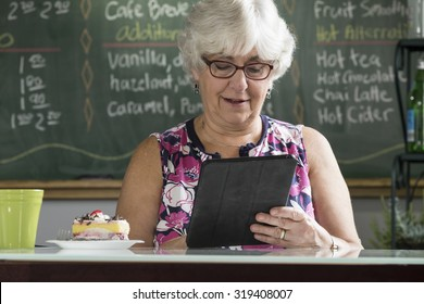 Senior woman using an ipad/tablet in a cafe
