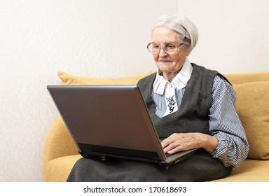 Senior woman using laptop computer while sitting on sofa