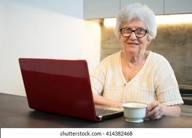 Senior woman using laptop computer while having coffee break at home.