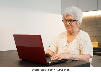Senior woman using laptop computer at home.