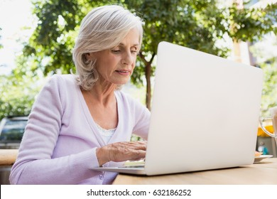 Senior woman using laptop in outdoor café on a sunny day