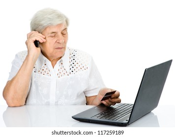 senior woman using laptop,  talking on cell phone and holding credit card. isolated on white background