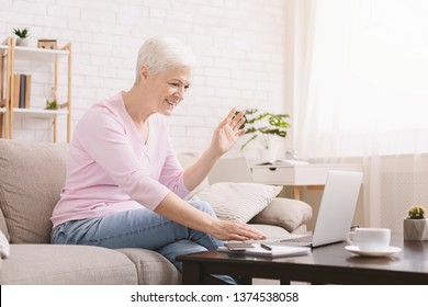 Senior woman using laptop for video call with her far living family, empty space