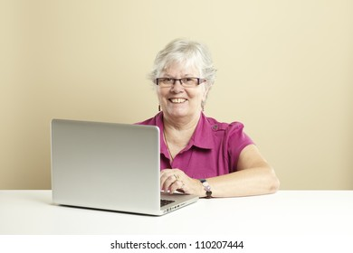 Senior woman using laptop whilst smiling
