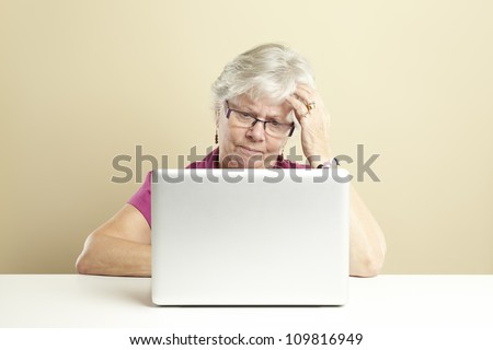 Senior woman using laptop whilst looking confused