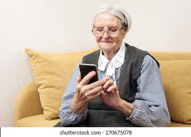 Senior woman using mobile phone while sitting on sofa