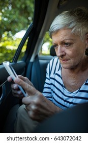 Senior woman using mobile phone while sitting in car