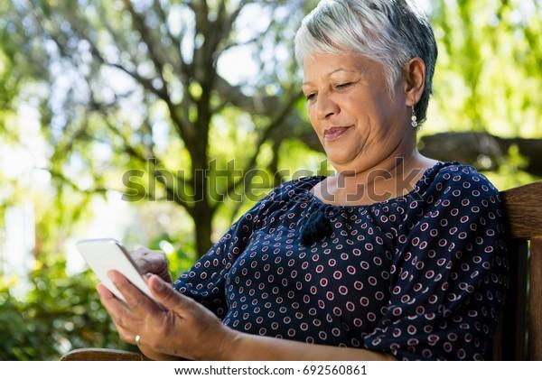 Senior woman using mobile phone in the garden