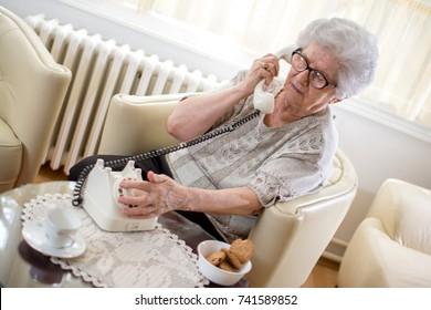 Senior woman using rotary phone at home.