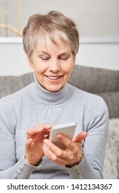 Senior woman using smartphone to chat and write message