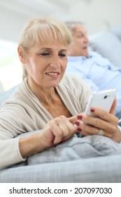 Senior woman using smartphone, husband reading book
