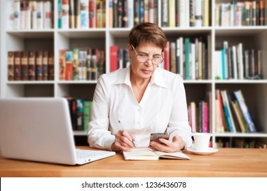 Senior woman is using a smartphone  sitting at a table