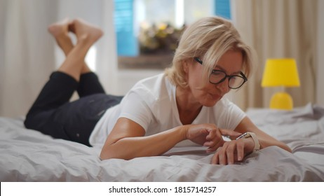 Senior woman using smartwatch relaxing on bed at home. Portrait of mature smiling lady using app or reading email on smartwatch lying on bed in cozy bedroom