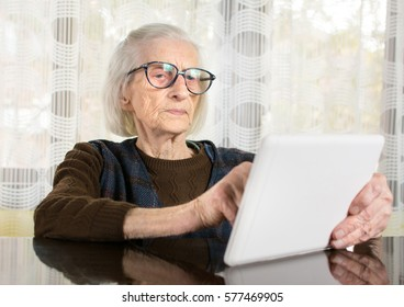 Senior woman using tablet device at home