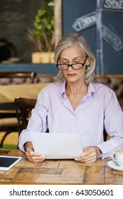 Senior woman using tabletv while sitting at table in cafe shop
