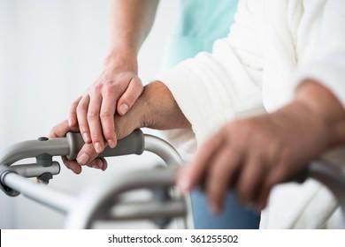 Senior woman using walking frame and helpful hand