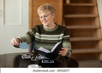 Senior woman viewing photo album in livingroom