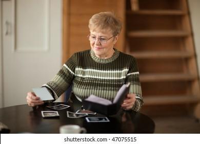 Senior woman viewing photo album in livingroom