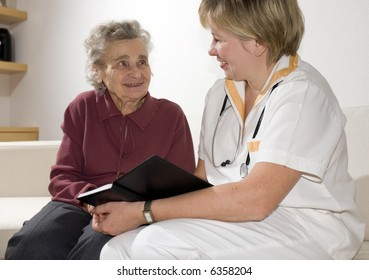 Senior woman is visited by doctor or caregiver