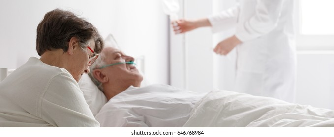 Senior woman visiting a dying man in hospital