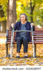 Senior woman with walker getting up from bench and walking outdoors in autumn park.
