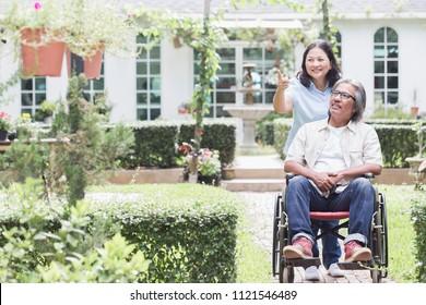 Senior woman walking with disabled father in garden. Happy Asian senior couple care together with wheelchair.  Adaptation of the Elderly Society or caring for the elderly or disabled concept.