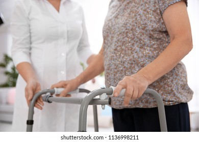 Senior woman with walking frame and caregiver at home, closeup