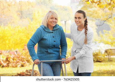 Senior woman with walking frame and young nurse in park