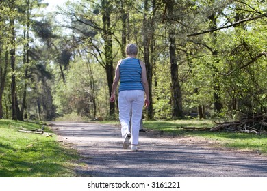 Senior woman walking with her back to the camera