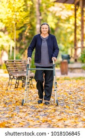 Senior woman walking outdoors with walker in autumn park and smiling at camera.