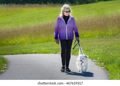 Senior woman walking a small brown dog up a hill on a path in a park on a sunny summer day