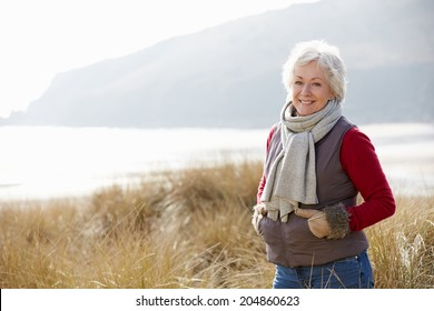 Senior Woman Walking Through Sand Dunes On Winter Beach