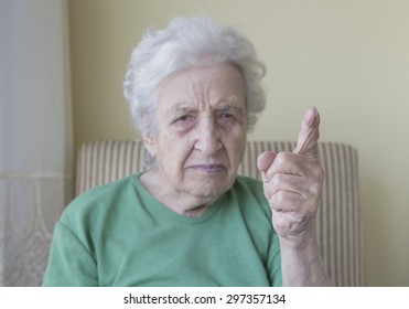 senior woman warning with her finger up