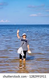 Senior woman waving hands at Baltic Sea in Jurmala in Latvia.