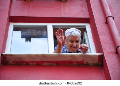senior woman waving her hand from window