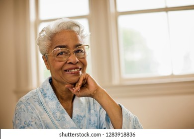 Senior woman wearing a bathrobe smiles and leans her chin on her hand as she sits in front of a window and poses for a portrait.