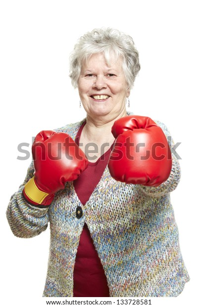 Senior woman wearing boxing gloves smiling on white background