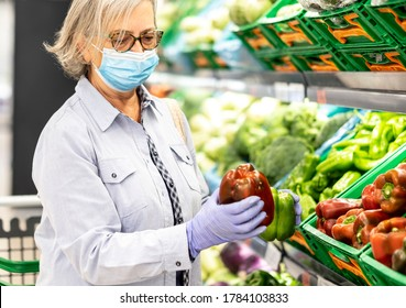Senior woman wearing face mask and rubber gloves selects peppers and other vegetables  in a supermarket -safe and healthy pensioner concept