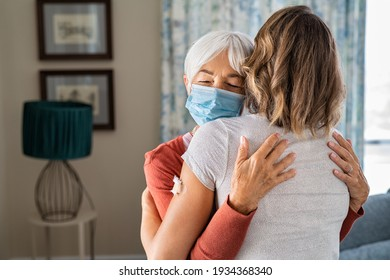 Senior woman wearing face mask hugging immunized daughter after covid-19 vaccination shot. Elderly grandmother hugging adult granddaughter after covid vaccine jab. Immunity and end of covid19 pandemic