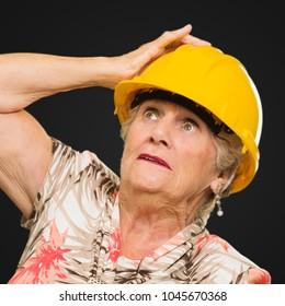 Senior Woman Wearing Hard Hat On Black Background
