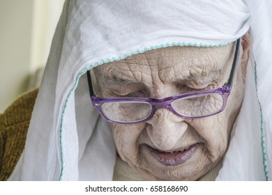 senior woman wearing headscarf while praying