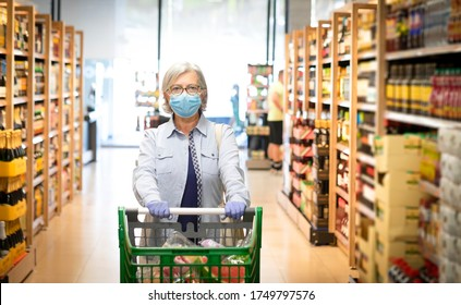 Senior woman wearing mask and rubber gloves pushes the shopping cart in a supermarket, in the wine department - active elderly pensioners, the window in background