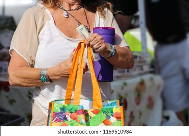 Senior woman wearing Native American - boho jewlery with bright shopping bag and water bottle and holding USD bills at outdoor market - unrecognizable and blurred background