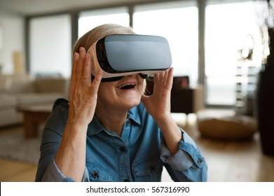 Senior woman wearing virtual reality goggles at home