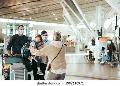 Senior woman welcoming her daughter and family  with open arms at airport arrival gate. Traveler family of three welcomed by grandma at airport in pandemic.