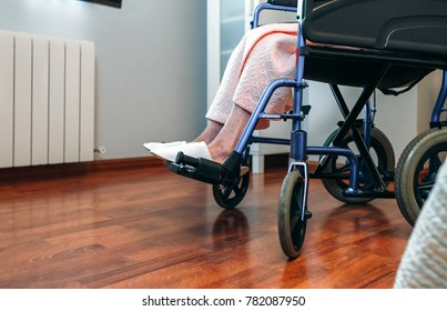 Senior woman in a wheelchair alone in a room