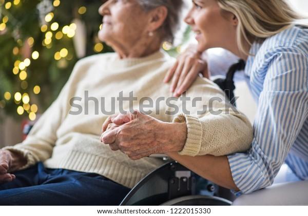 Une femme âgée en fauteuil roulant avec un visiteur de santé à la maison à Noël.