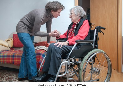 Senior woman with wheelchair and helping caregiver