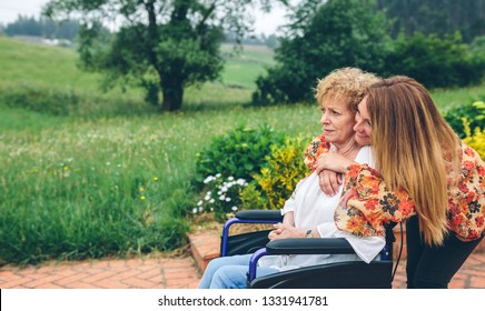 Senior woman in a wheelchair with her daughter in the garden