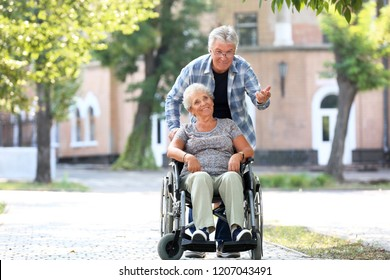 Senior woman in wheelchair and her husband outdoors
